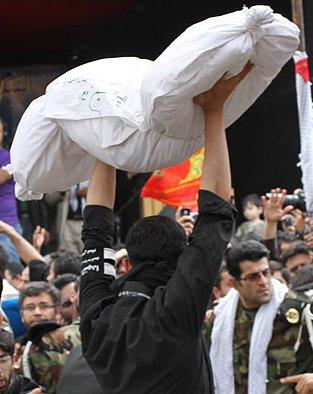 شهید گمنام بر روی دستان محمدبازلی ( یک رزمنده نسل سومی)